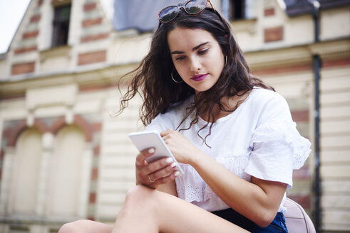 Portrait of young woman using cell phone outdoors - ABIF00755