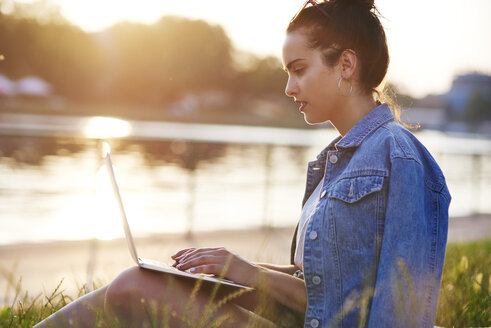 Young woman sitting on a meadow at evening twilight using laptop - ABIF00758