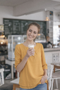 Young business owner standing in her coffee shop, drinking coffee - JOSF02326