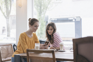 Two girlfriends meeting in a coffee shop, using smartphone - JOSF02335