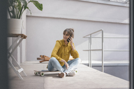 Young woman sitting on skateboard, using smartphone - JOSF02356