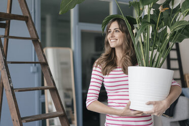 Woman holding potted plant in her bew home - JOSF02365