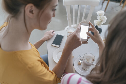 Two girlfriends meeting in a coffee shop, using smartphone - JOSF02386