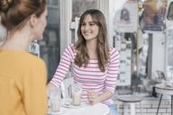 Two girlfriends meeting in a coffee shop, talking - JOSF02395