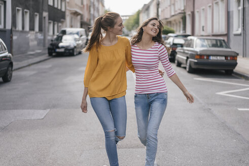 Two girlfriends having fun in the city, walking arm in arm - JOSF02398