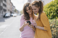 Friends in the city using smartphone, reading text messages - JOSF02404