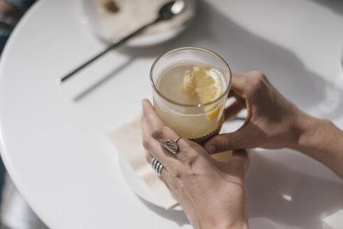 Woman holding glass of ginger lemon tea - JOSF02407