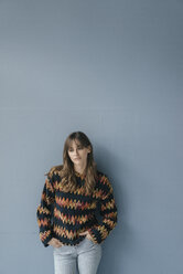 Sad young woman leaning against wall, with hands in pockets - JOSF02410