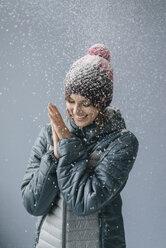 Woman wearing woolly hat in snow, portrait - JOSF02413