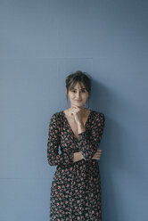 Woman with flower dress leaning against wall, portrait - JOSF02416