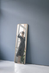 Young woman in vintage dress looking into mirror - JOSF02419