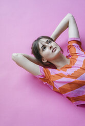 Woman lying on pink background with hands behind head, thinking - JOSF02422