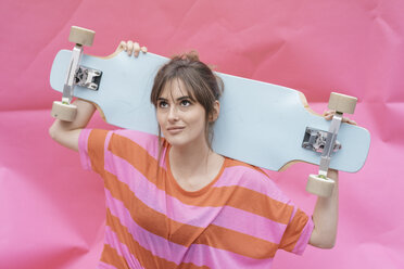 Woman holding skateboard, looking up - JOSF02425
