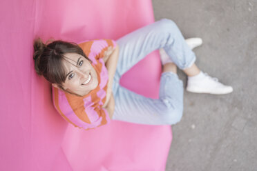 Confident young woman sitting on pink background - JOSF02428