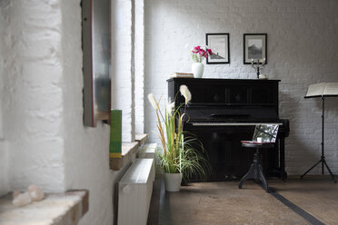 Piano with laptop on a stool in comfortable loft apartment - FKF03034