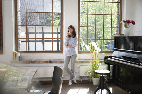 Woman standing at window of her loft apartment, drinking coffee - FKF03052