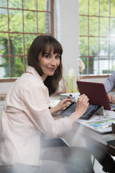 Mature woman sitting in home office, using digital tablet - FKF03073