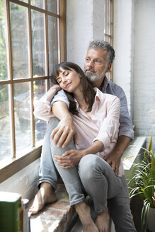 Mature couple sitting on window sill, looking out of window - FKF03082