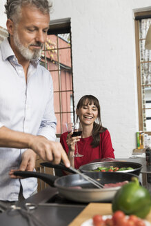 Woman sitting in kitchen, drinking red wine, watching man preparing food - FKF03094