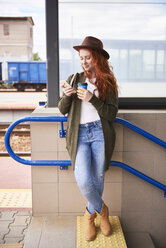 Smiling redheaded woman with coffee to go looking at cell phone at platform - ABIF00762