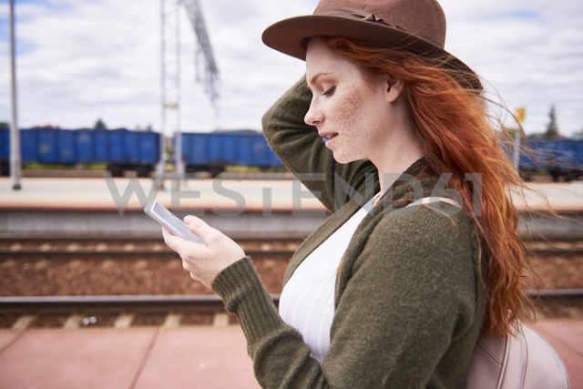 Redheaded woman at platform looking at cell phone - ABIF00768