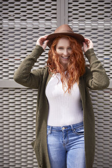 Portrait of smiling redheaded woman with brown hat - ABIF00771