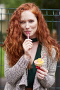 Portrait of smiling redheaded woman eating icecream - ABIF00777