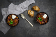 Two bowls of Chili con Carne with fresh coriander and sour cream - LVF07339