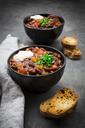 Two bowls of Chili con Carne with fresh coriander and sour cream - LVF07342