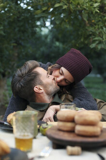 Apple orchard. A couple kissing, food and drink on a table. - MINF02301