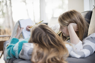 Two girls lying on a sofa, one writing into a notebook with a pencil. - MINF02304