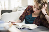Young woman sitting on a sofa, reading a book. - MINF02307