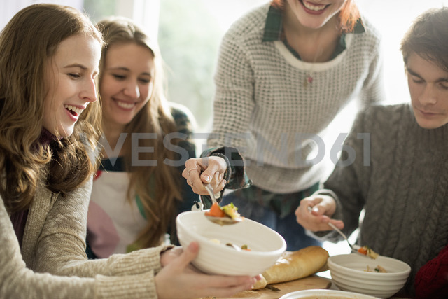 Four people sitting and standing at a table, a woman serving food into a bowl. - MINF02313