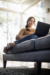 Low angle view of a woman sitting on a sofa looking at her laptop. - MINF02319