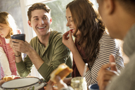 A group of people sitting at a table, smiling, eating, drinking and chatting. - MINF02328