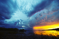 Sunset on the horizon over a lake, and storm clouds rising. - MINF02355