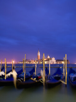 A view from the Riva degli Schiavoni and the Piazza San Marco across the water to the island and church of San Giorgio Maggiore. Gondolas moored at dusk. - MINF02364