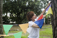 A woman in a Kyoto park holding up a colourful row of flags. - MINF02529