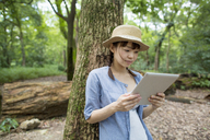 Young woman holding a digital tablet in a forest. - MINF02607