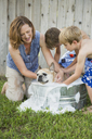 A family in their garden, washing a dog in a tub. - MINF02637