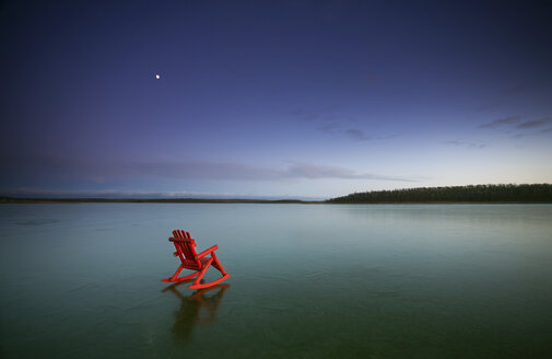 A small red rocking horse, on a frozen lake. - MINF02655