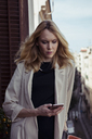 Portrait of blond young woman looking at cell phone - MAUF01520