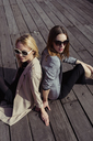 Portrait of two fashionable young women sitting on wooden floor wearing sunglasses - MAUF01529