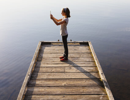 A young girl holding a digital tablet in front of her, standing on a wooden dock over the water. - MINF02778