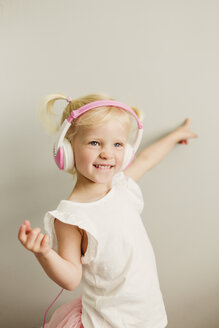 Portrait of blond little girl with headphones dancing - NMSF00207