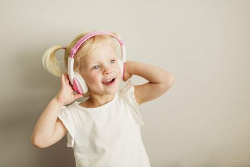 Portrait of little girl listening music with headphones dancing - NMSF00210