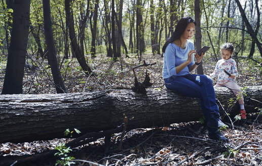 Mother and daughter in park,sitting on tree trunk,  using smartphone - AZF00020