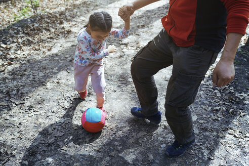 Father and daughter playing football in park - AZF00026