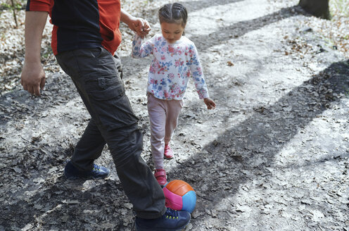 Father and daughter playing football in park - AZF00029