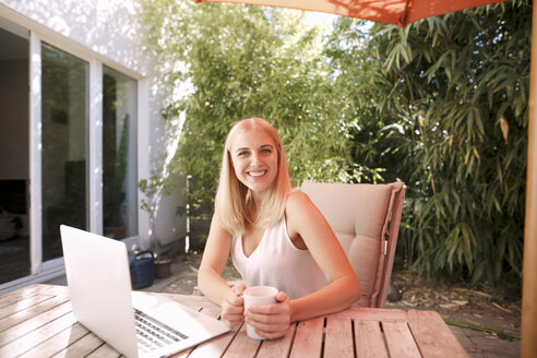 Young smiling woman using laptop, sitting on garden table - KMKF00406
